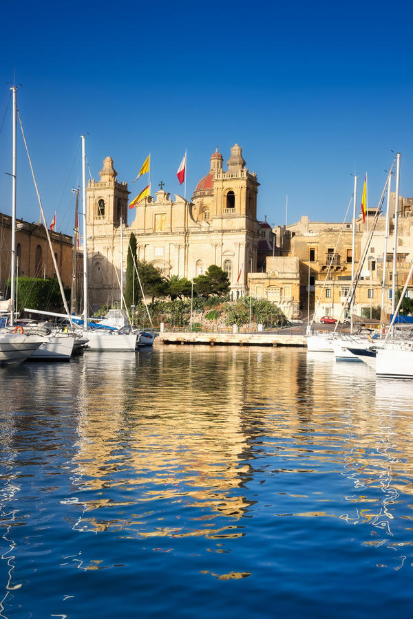 Vittoriosa, Collegiate church of St Lawrence. Over the water of Dockyard creek with sailing boats on a sunny afternoon stock photography