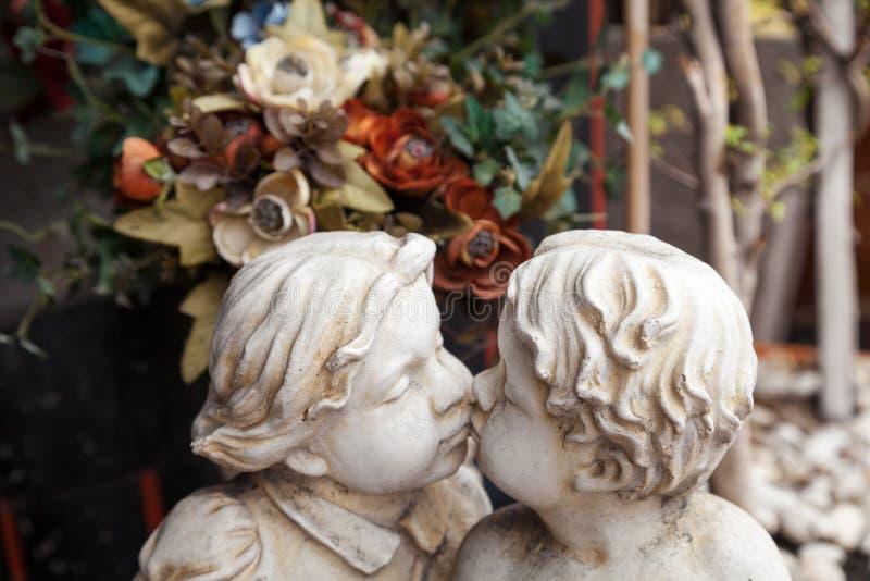 Vitträdgårdskulptur av två kyssa ungar Barnänglar för lockigt hår som kysser konststatyn av murbruk royaltyfri foto