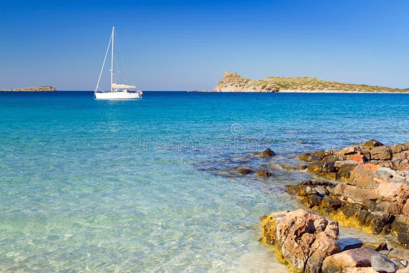 Vityacht på den idylliska strandlagunen av Crete royaltyfri foto