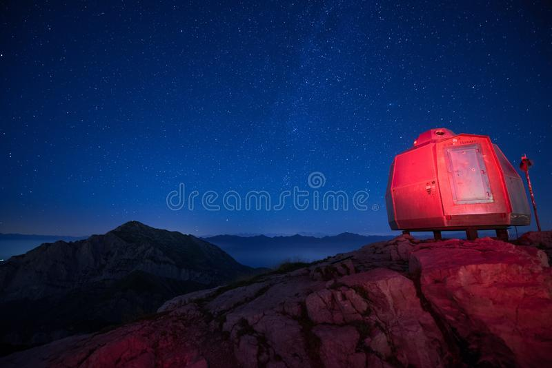 Vivac encendida roja en las monta?as altas debajo de un cielo estrellado hermoso fotografía de archivo
