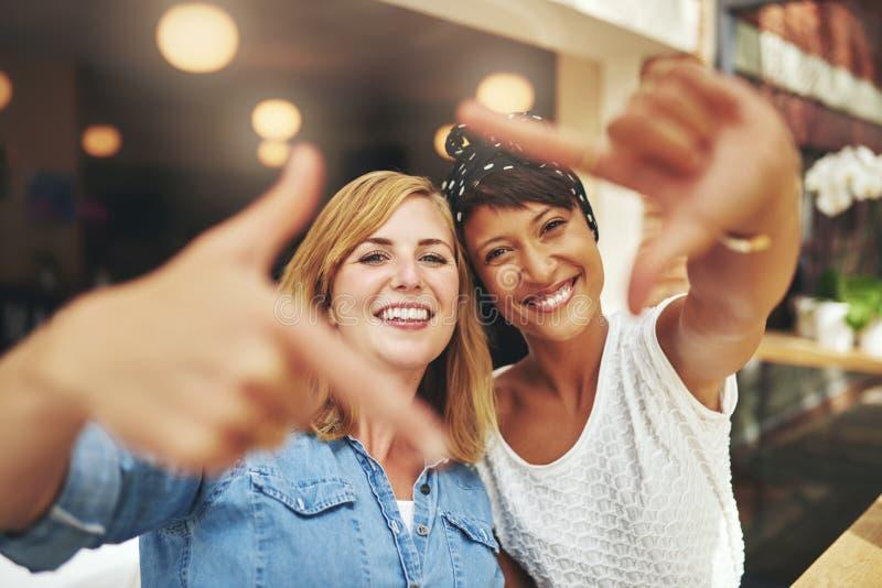 Vivacious молодые женщины обрамляя их стороны стоковая фотография rf