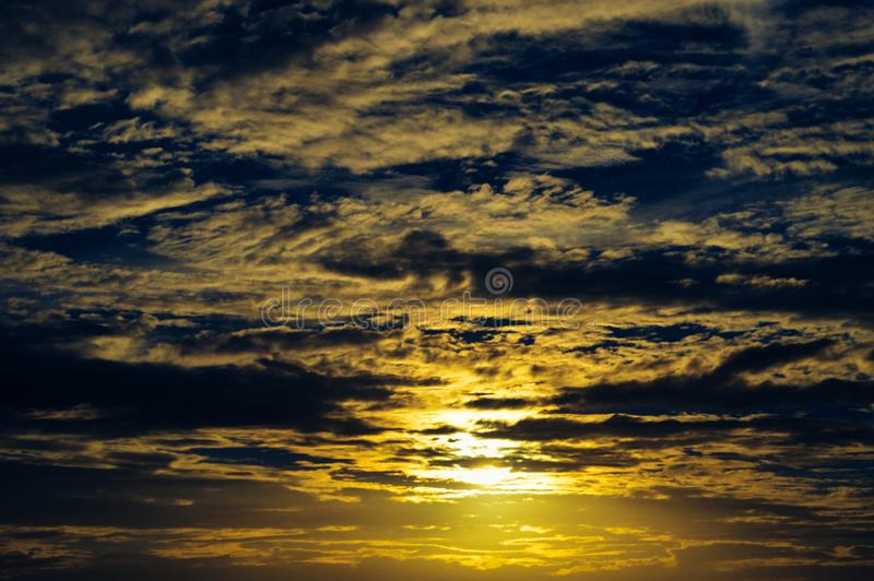 Vivid gray clouds at sunset with a dark blue sky stock images