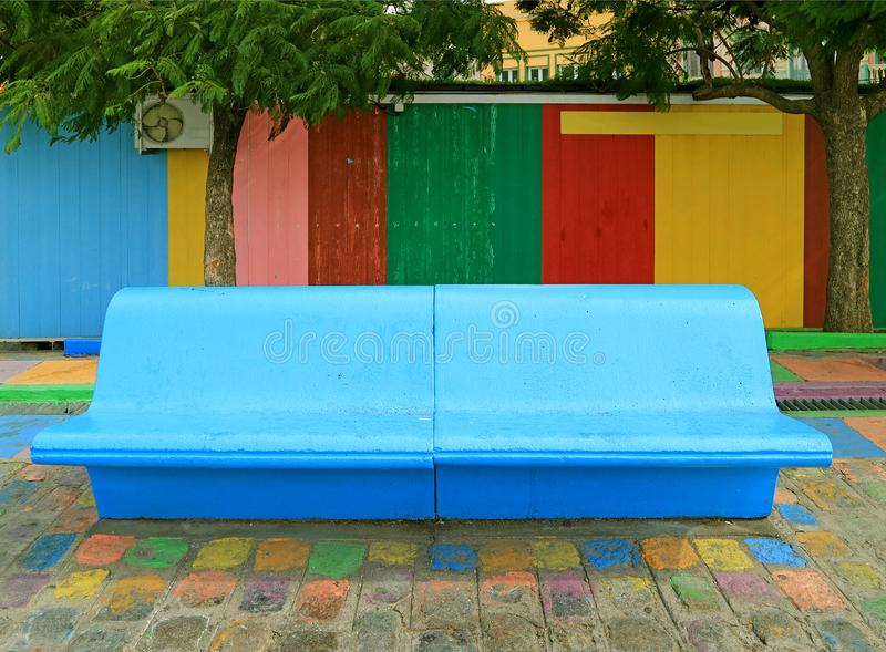 Vivid Blue Concrete Bench in front of Colorful Wooden Wall at La Boca Neighborhood of Buenos Aires, Argentina. South America aged architecture attraction stock image