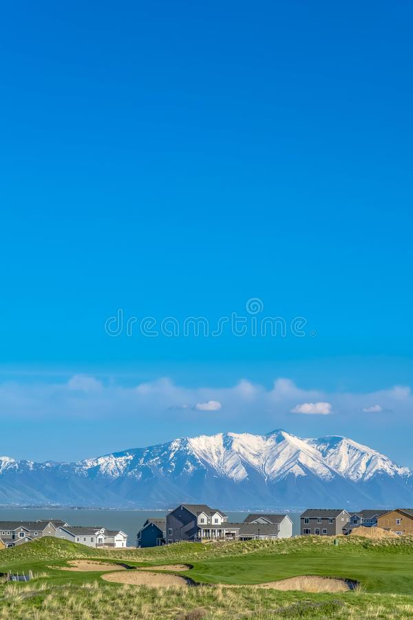 Vivid blue sky with clouds over a lake and snow capped mountain on a sunny day royalty free stock photos