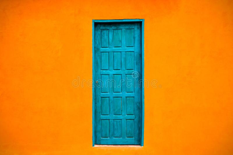 Vivid bright orange colour facade with blue-green closed door in the center of large empty orange wall royalty free stock photo