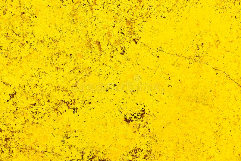 Vivid bright yellow color facade stone wall with imperfections and cracks as an empty rustic and simple background. Texture space royalty free stock images