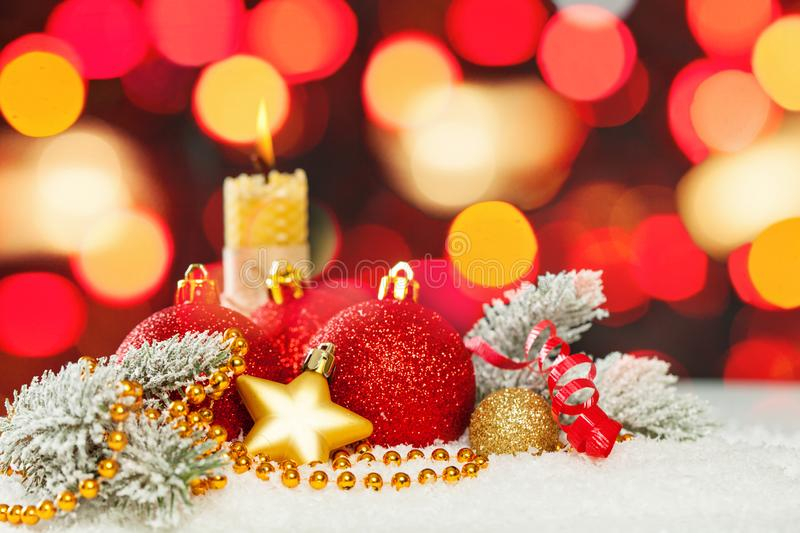 Vivid Christmas composition with red and gold bokeh light, green fir branch, garland, baubles and ribbon on white snow background.  stock photos