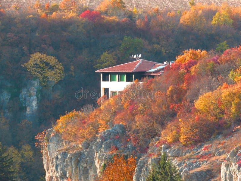 Vivid colourful yellow red orange autumn fall season. Small cottage house in mountains on the rocks surrounded by trees. Vivid colourful yellow, red orange royalty free stock image