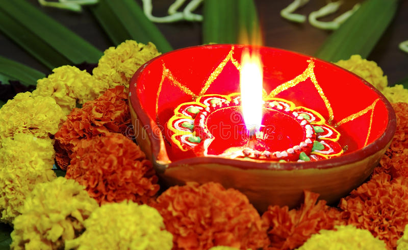 Vivid colours Diwali marigolds diva candle lamp. Angled view. Rangoli, floral design display Hindu Festival by womenfolk a custom done outdoors or indoors during royalty free stock photography