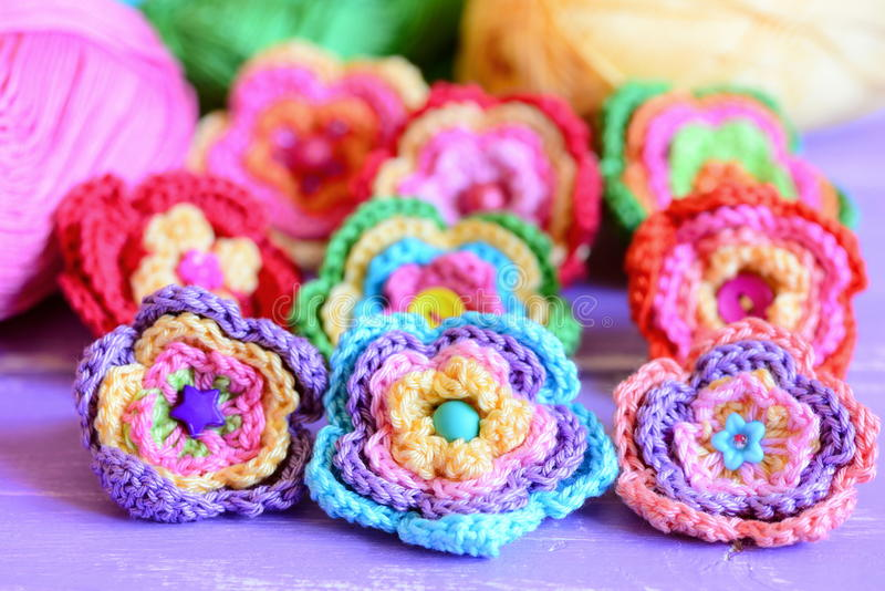 Vivid crochet flowers on purple wooden background. Crocheted flowers from colourful cotton yarn. Easy summer handmade crafts idea royalty free stock images