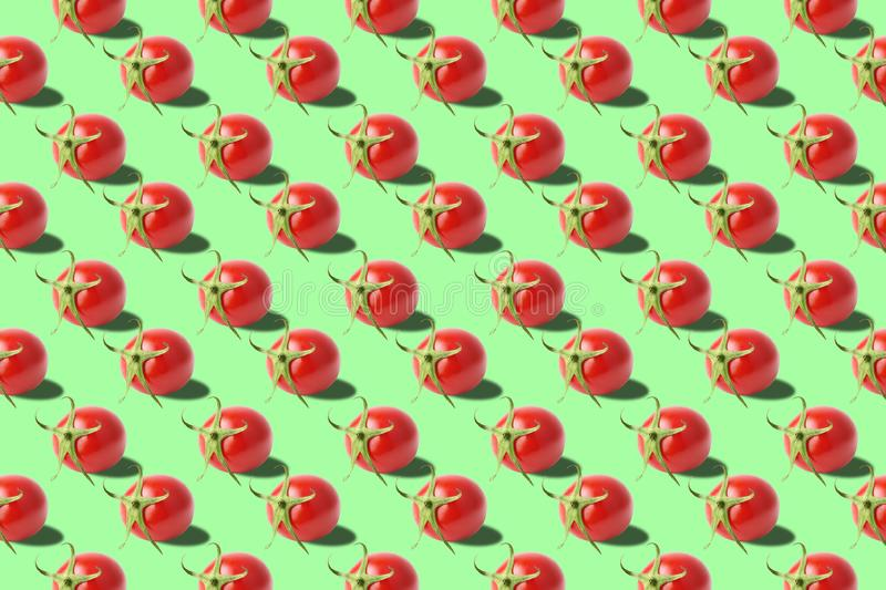 Vivid fresh vegetables pattern on colourful background. Tomatoes texture on green background. From top view. full depth of field. Minimal summer fruits pattern stock image
