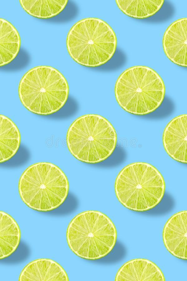 Vivid fruit pattern of fresh lime on colourful background. Colorful fresh slices lime texture on light blue background. From top view. full depth of field stock photo