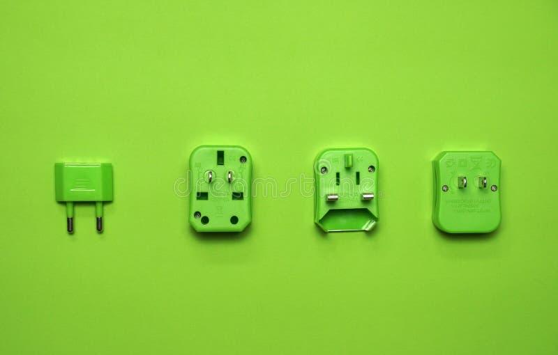 Vivid green universal wall electric plug adapter aboard travel set for tourist monochrome photo stock photos
