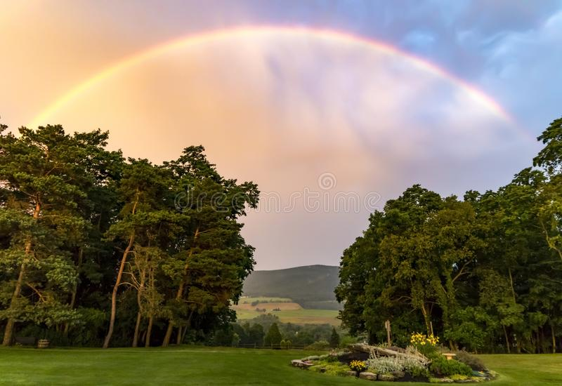 Vivid Rainbow Over Valley. A beautiful rainbow over a mountain valley and trees as the sky begins to clear after a storm royalty free stock photography