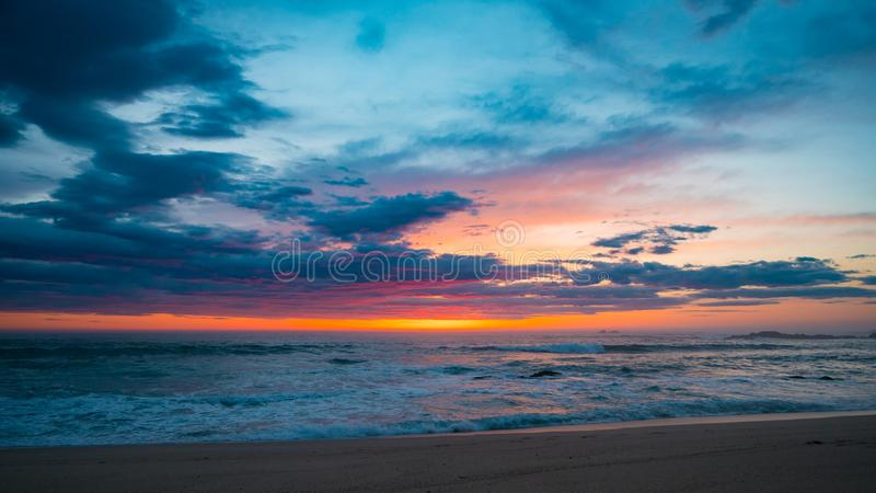 Vivid red sky at sunset on the beach with dark clouds. And orange blue gradient sky royalty free stock image