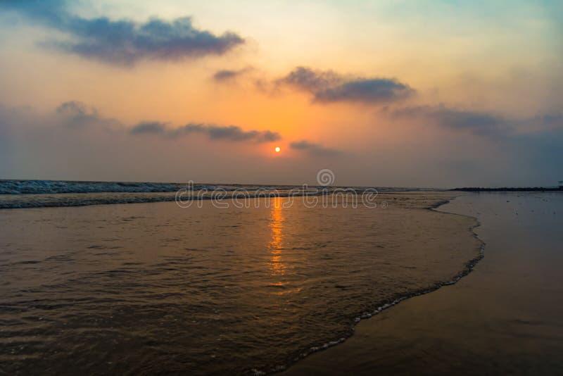 Vivid sunrise on a serene calm tranquil deserted beach at digha stock photos