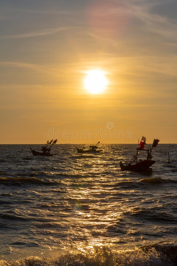 Vivid twilight sunset sky and motion blur of the sea under with long exposure effect. Beautiful golden sunset in the sea with saturated sky and clouds royalty free stock images