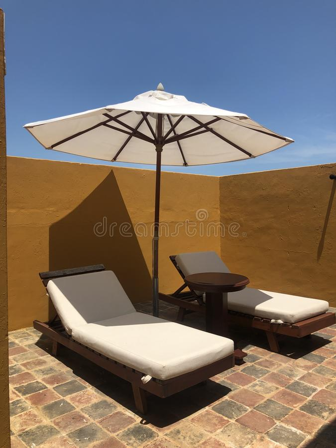 Lounge chairs and Shade Umbrella. Vivid yellow painted adobe wall with lounge chairs and umbrella to shade from the heat of the sun royalty free stock image