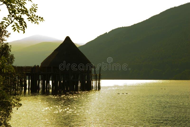Vivienda antigua del lago de Crannog, puesta del sol imagenes de archivo