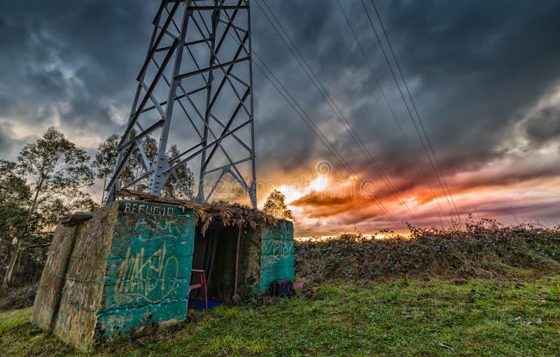 Vivienda pobre, un refugio debajo de una torre eléctrica fotos de archivo libres de regalías