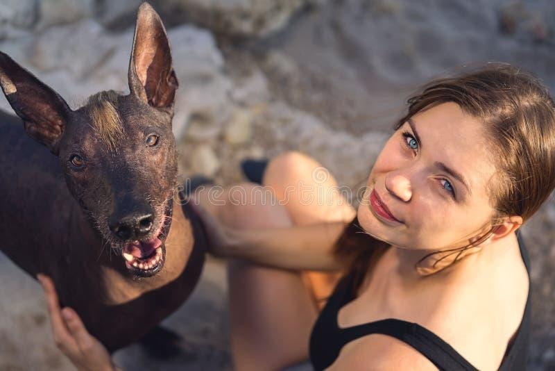 Viw superiore di bella ragazza e suo del xoloitzcuintle della razza del cane che sorridono su un'estate di pietra della spiaggia fotografia stock