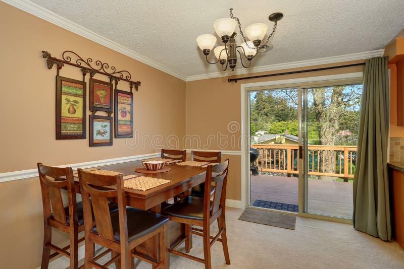 Viwe da tabela de madeira ajustou-se na sala de jantar com paredes do mocha fotos de stock royalty free