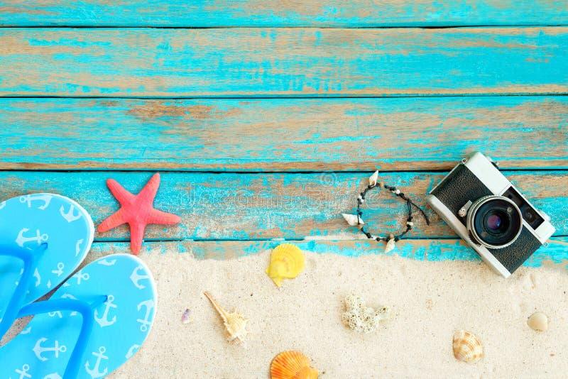 Viwe superior de la arena de la playa con el deslizador, las estrellas de mar, las cáscaras, el coral, el camara retro y la pulse fotos de archivo