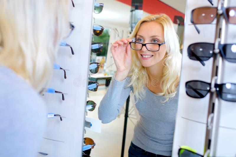 Viyoung aantrekkelijke vrouw die glazen proberen bij opticien stock foto