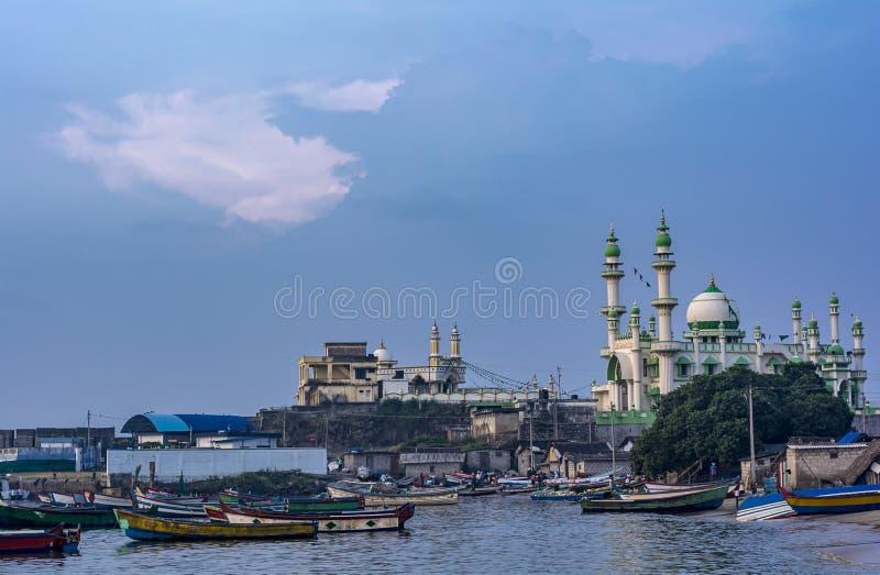 Vizhingam口岸的清真寺与小船和天空蔚蓝背景 库存照片