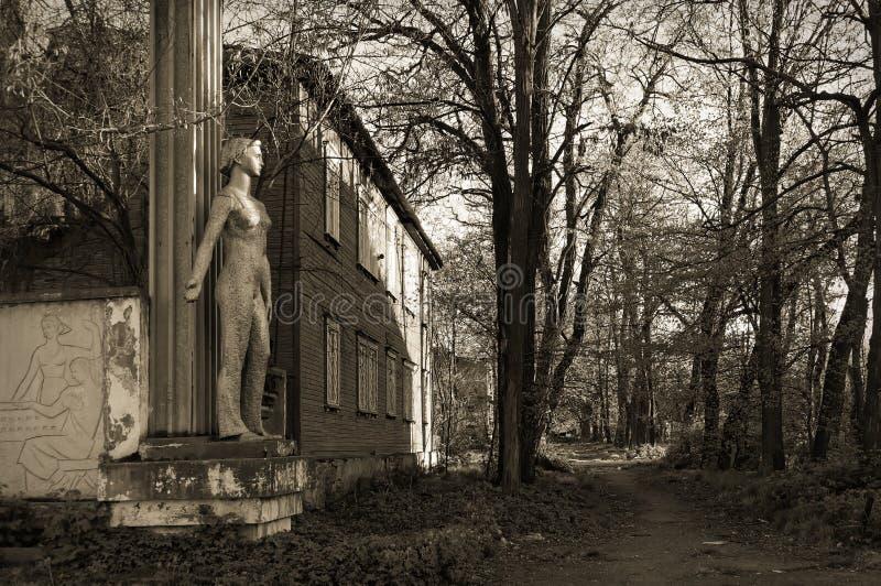 Vladikavkaz norr Ossetia, Ryssland - 2016 04 17: Tillbaka i USSR En staty av en arbetarkvinna bredvid den Dinamo växten i Vladika arkivfoton