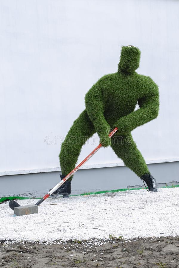 Vladimir, Russia April 18, 2019 Vladimir Blagonravova street 1, sculpture of a hockey player made of artificial grass at the stock photography