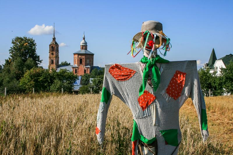 Scarecrow on a wheat field on the background of old churches and villages. Village landscape. 2009.08.29, Vladimir, Russia. Scarecrow on a wheat field on the royalty free stock photography