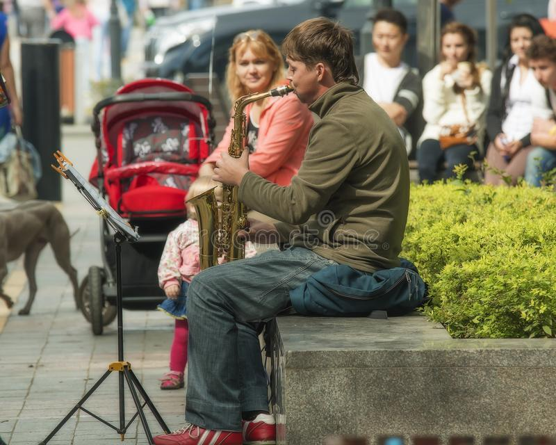 People listen to a street musician. Vladivostok,Primorsky Krai,Russia 09272015 street musician playing the saxophone on the waterfront of the city of Vladivostok royalty free stock photography