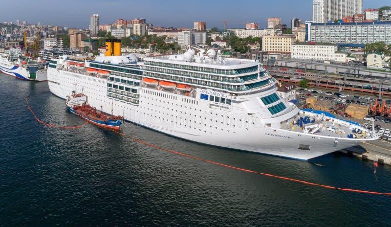 Vladivostok, Rússia - 30 de maio de 2017: Os depósitos do petroleiro de Atlant o navio de cruzeiros Costa NeoRomantica no cais em fotografia de stock