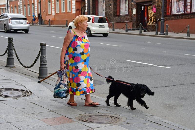 Vladivostok, Rússia, julho, 29,2018 Mulher idosa com um cão preto que anda abaixo da rua no verão imagens de stock
