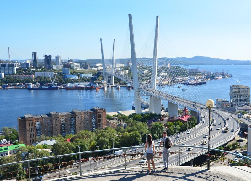 Vladivostok, Russia, August, 31, 2017. The guy with the girl admiring the cable-stayed bridge across the Zolotoy Rog Bay in Septem royalty free stock photo