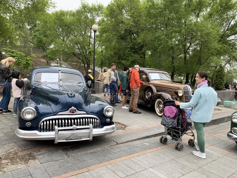 Vladivostok, Russia, May, 18, 2019. People walking on Exhibition of American retro-cars near Buick Road Master 1950 year and Dodge stock photography