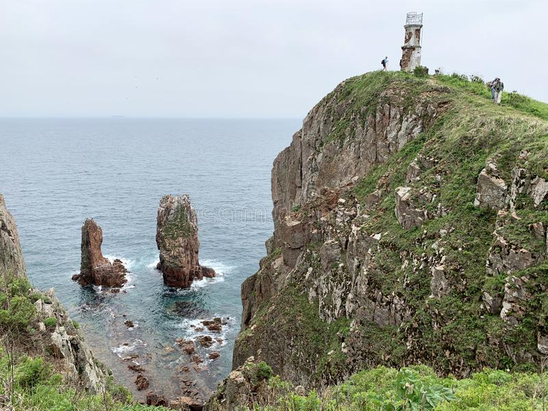 Vladivostok, Russia, June, 02, 2019. Tourists hiking on island of Shkot in cloudy weather near old lighthouse. Vladivostok, Russia. Tourists hiking on island of stock image