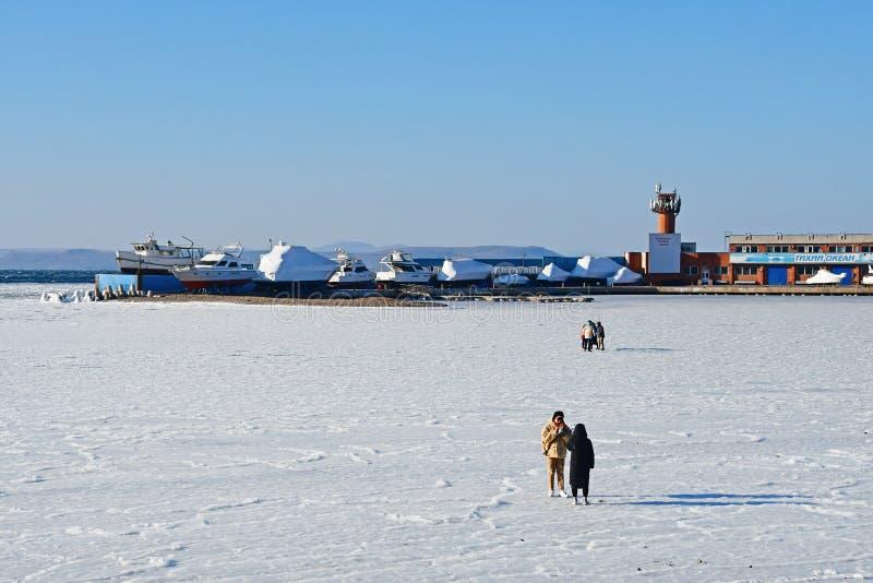 """Vladivostok, Russie, décembre, 30, 2018 Les gens marchant dans la baie d'Amur en hiver près du club de yacht """"l'océan pacifique """" image libre de droits"""