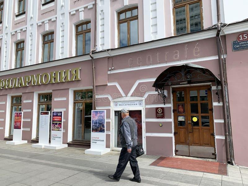 Vladivostok, Russie, mai, 22, 2019 Homme marchant près du bâtiment philharmonique sur la rue de Svetlanskaya dans Vladivostok image libre de droits