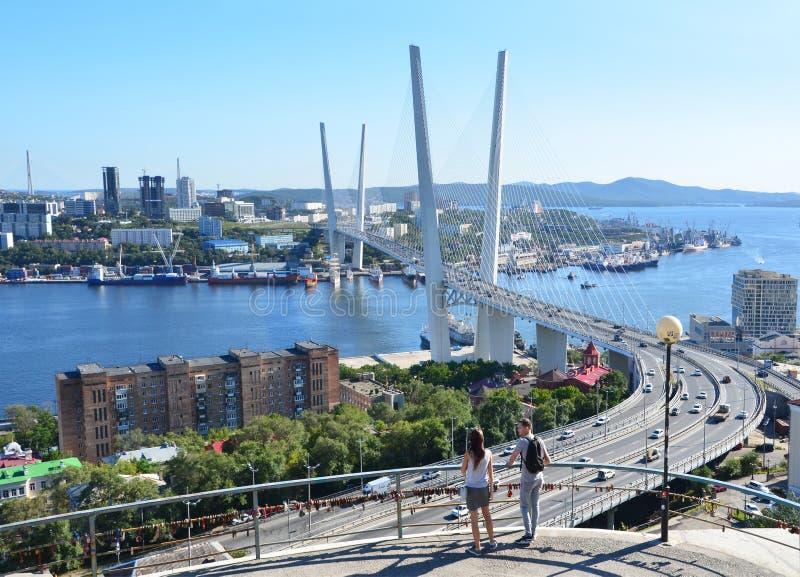Vladivostok Ryssland, Augusti, 31, 2017 Grabben med flickan som beundrar denblivna bron över Zolotoyen Rog Bay i Septem royaltyfri foto