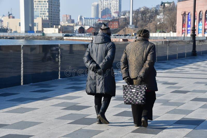 Vladivostok Ryssland, Januari 19, 2019 Två äldre kvinnor som promenerar invallningen av kronprinsen Tsesarevich i solig seger arkivbild