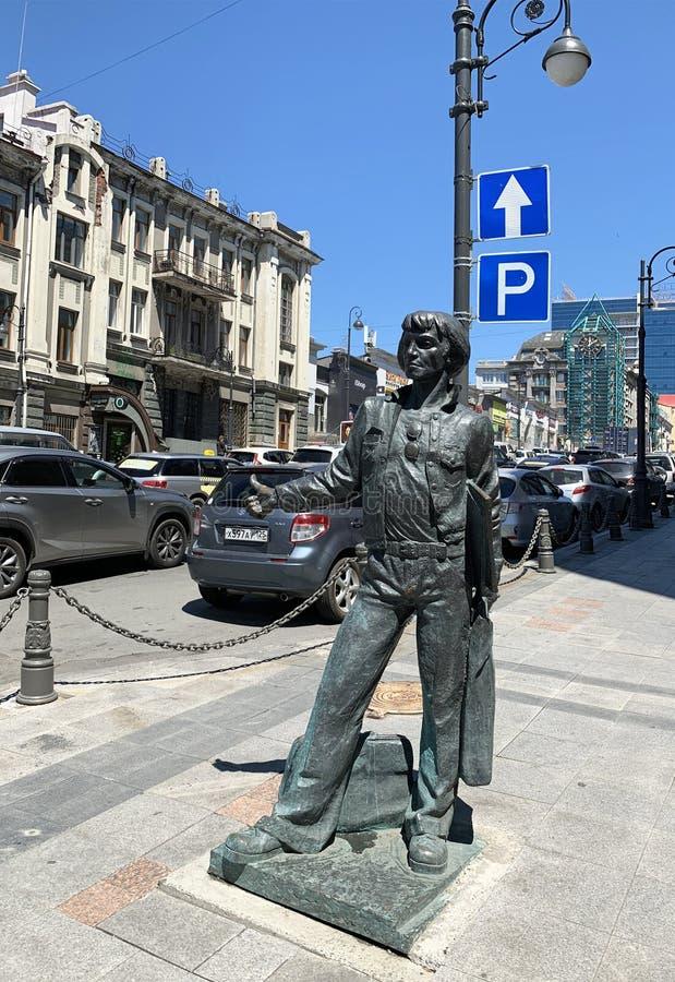 Vladivostok Ryssland, Maj, 23, 2019 Monumentet 'brons sjömannen fångar en taxi 'mot den blåa himlen på havavenyn Vladivostok, royaltyfria bilder