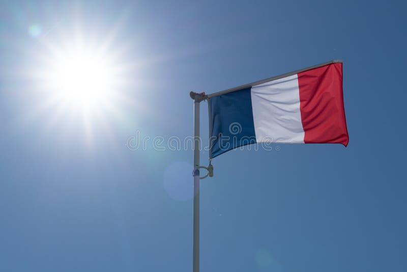 Vlag die van Frankrijk over blauwe hemel en grote zon golven stock foto's