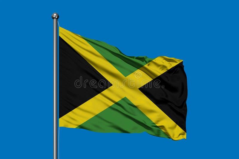 Vlag die van Jama?ca in de wind tegen diepe blauwe hemel golven Jamaicaanse vlag stock afbeelding