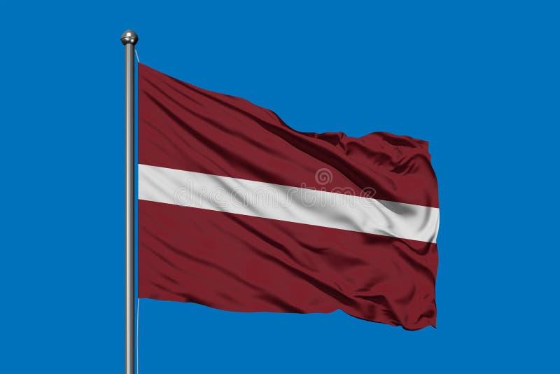 Vlag die van Letland in de wind tegen diepe blauwe hemel golven Letse vlag stock afbeelding