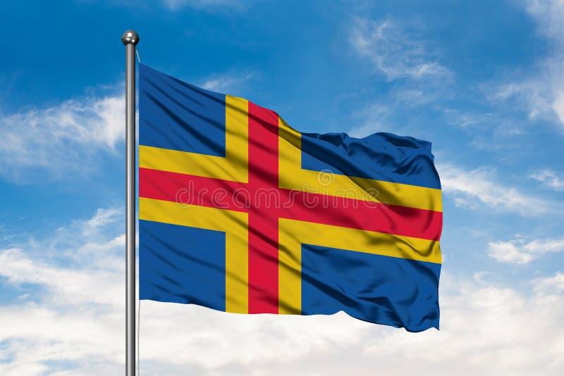 Vlag van Aland-Eilanden die in de wind tegen witte bewolkte blauwe hemel golven stock afbeelding