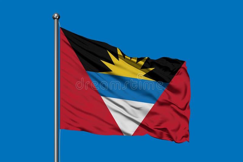 Vlag van Antigua en Barbuda die in de wind tegen diepe blauwe hemel golven royalty-vrije stock afbeeldingen