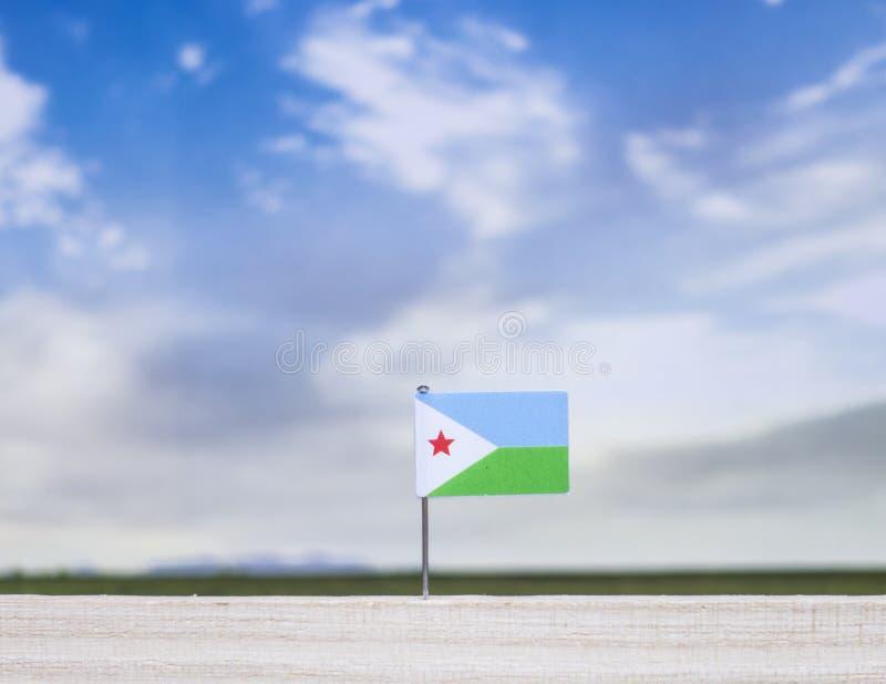 Vlag van Djibouti met enorme weide en blauwe hemel achter het stock foto's