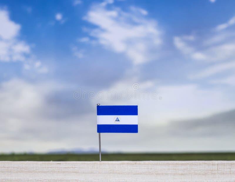 Vlag van Nicaragua met enorme weide en blauwe hemel achter het royalty-vrije stock foto's